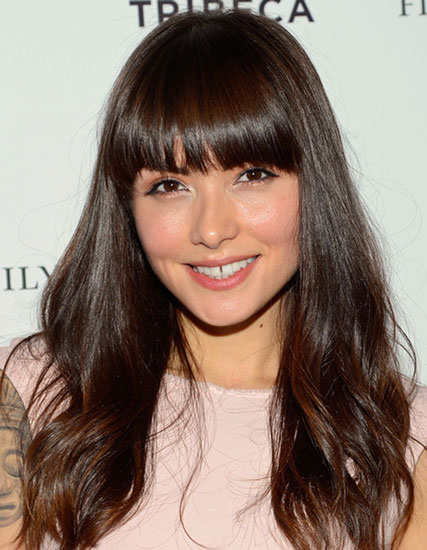 Daniella Pineda's Cute Long Wavy Hair with Blunt Bangs