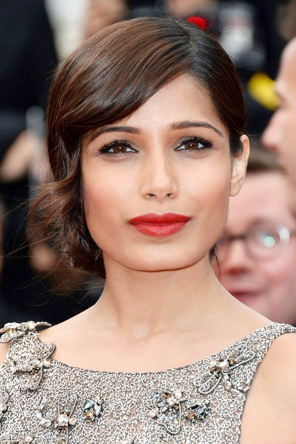 Freida Pinto's Vintage Low Bun Hairstyle with Face Framing Curls
