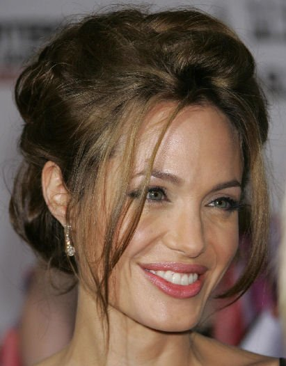 Angelina Jolie's Long Wavy Hair Is In A Loose Updo.