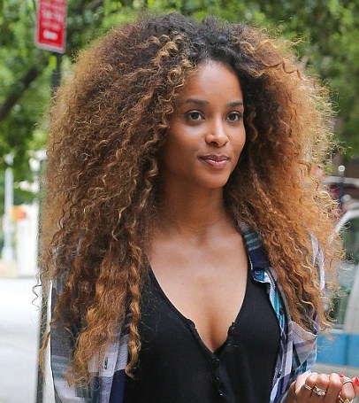 Ciara s long brown hair in very curly afro with highlights