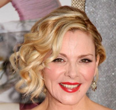 Kim Cattrall's Blonde Curly Hair In Sideswept Formal Hairdo